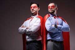 knappe super zakenlieden in maskers en kaap die zich met gekruiste wapens bevinden stock fotografie