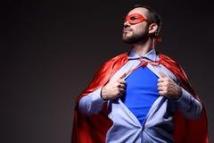 knappe super zakenman in masker en blauw overhemd tonen en kaap die weg eruit zien royalty-vrije stock afbeeldingen