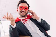 knappe super zakenman in masker en kaap die door smartphone spreken royalty-vrije stock afbeeldingen