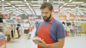 Knappe supermarktbediende die een tablet van het aanrakingsscherm in supermarkt gebruiken stock videobeelden
