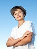 Knappe tiener die zich buiten tegen een blauwe hemel bevinden Stock Foto's