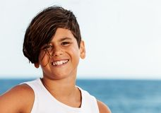 Knappe tiener Spaanse jongen tegen zeegezicht stock foto's