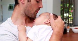 Knappe vader die zijn baby houden stock videobeelden
