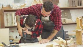 Knappe vader en zijn tienerzoon die met boor op workshop werken stock footage