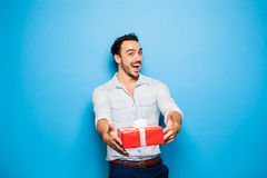 Knappe volwassen mens op blauwe achtergrond met Kerstmisgift Stock Afbeeldingen