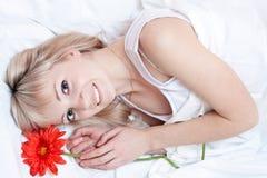 Knappe vrouw in bed stock afbeelding