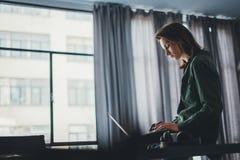 Knappe vrouwelijke medewerkerzitting bij de lijst en het gebruiken van laptop computer Het werk proces bij het coworking van stud royalty-vrije stock afbeeldingen