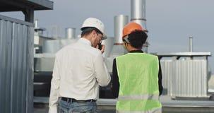 Knappe vrouweningenieur en rijpe man ingenieur die het plan van het voortbouwen op het dak van bouwwerf analyseren stock footage