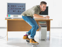 Knappe werknemer die door het bureau schaatsen Stock Afbeelding