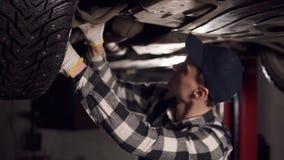 Knappe werktuigkundige die heel wat inspanning zetten in het bevestigen van alle autoproblemen De autodienst, reparatie, onderhou stock footage