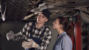 Knappe werktuigkundige die zijn vrouwelijke cliënt alle problemen in haar voertuig tonen, die op sommige mechanismen op de bodem  stock footage