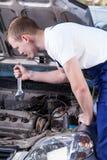 Knappe werktuigkundige met moersleutel het bevestigen auto Stock Foto's