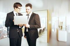 Knappe zakenlieden die laptop samen met behulp van Royalty-vrije Stock Afbeeldingen