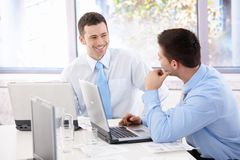 Knappe zakenlieden die in vergaderzaal babbelen Stock Foto
