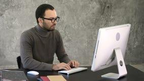 Knappe zakenman die aan computer in bureau werken stock video