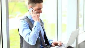 Knappe zakenman die bij telefoon spreken stock videobeelden