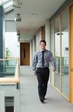 Knappe zakenman die door een gang loopt Stock Foto
