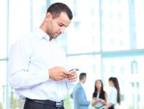 Knappe zakenman die een smartphone gebruiken Stock Fotografie