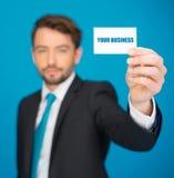 Knappe zakenman die leeg adreskaartje tonen Stock Fotografie
