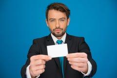 Knappe zakenman die leeg adreskaartje tonen Stock Foto