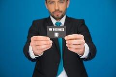 Knappe zakenman die leeg adreskaartje tonen Royalty-vrije Stock Afbeeldingen