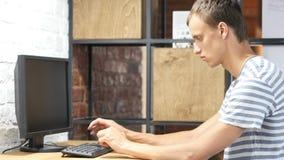 Knappe zakenman die met computer in bureau werken stock videobeelden