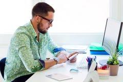 Knappe zakenman die mobiele telefoon in bureau met behulp van Stock Foto's