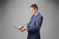 Knappe zakenman die moderne laptop houden Royalty-vrije Stock Fotografie