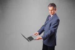 Knappe zakenman die moderne laptop houden Royalty-vrije Stock Afbeelding