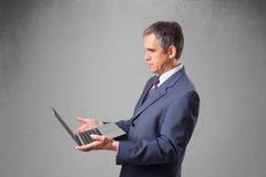 Knappe zakenman die moderne laptop houden Stock Afbeelding