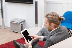 knappe zakenman die op digitale tablet richten stock afbeelding