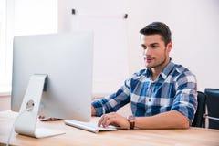 Knappe zakenman die PC met behulp van bij de lijst stock fotografie