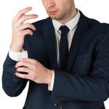Knappe zakenman die zijn manchetten aanpassen stock foto's
