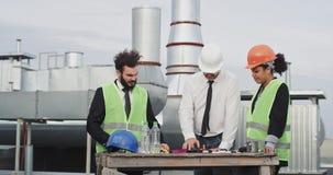 Knappe zakenman en ingenieur en zijn hulpdame die het plan van bouwwerf analyseren die spreken stock footage