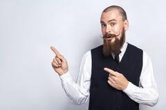 Knappe zakenman met baard en stuursnor die verraste camera bekijken, en exemplaarruimte met vingers tonen Stock Fotografie