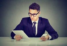 Knappe zakenman met gadgets bij lijst royalty-vrije stock afbeelding