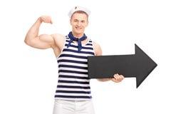 Knappe zeeman die bicep en een pijl houden tonen stock fotografie