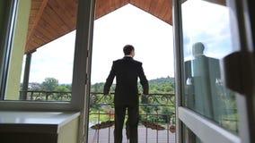 Knappe zekere bruidegom in zwart kostuum die zich op het balkon bevinden die bij het omheinen leunen en op het groene bos kijken stock videobeelden