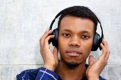 Knappe zwarte mens die aan muziek met hoofdtelefoons luisteren stock foto's