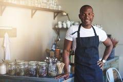Knappe zwarte ondernemerstribunes door koffieteller royalty-vrije stock fotografie