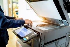 Knappen för press för handen för affärsmannen på panel av skrivaren, tillförsel för maskin för kopia för kontor för laser för skr fotografering för bildbyråer