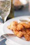 Knapperig gebraden verkruimeld kippengoudklompjes en wijnglas stock fotografie