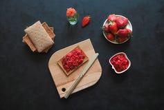 Knapperig roggebrood met aardbeijam op een zwarte lijst Aardbeiontbijt royalty-vrije stock fotografie