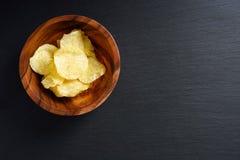 Knapperige chips in kom op zwarte achtergrond, hoogste mening, exemplaarruimte royalty-vrije stock foto