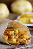 Knapperige gebraden aardappels met kruiden Heerlijke gebraden aardappels in document en op een houten lijst Eenvoudig aardappelre Stock Foto's