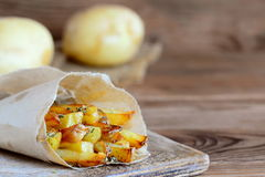 Knapperige gebraden aardappels met kruiden Land gebraden aardappels in document en op een houten lijst rustieke stijl Houten acht Royalty-vrije Stock Afbeelding
