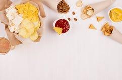 Knapperige gouden snacks op ambachtdocument, van driehoekennachos, van het lagerbierbier, rode en gele saus in kom op zachte witt stock foto