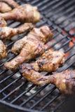 Knapperige Kippentrommelstokken op grillbbq Stock Foto