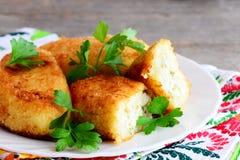 Knapperige plantaardige pasteitjes met ei het vullen op een witte plaat Gebraden die pasteitjes met mengeling gekookte groenten w Stock Foto
