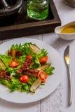 Knapperige salade met bacon en kers op een witte plaat stock afbeeldingen
